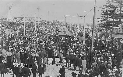 Crowds departing after arrival of American fleet August 1908. Lighthouse at extreme left. Trams are saturated with passengers.